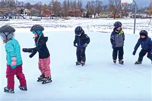 A group of small children ice skating outdoors.